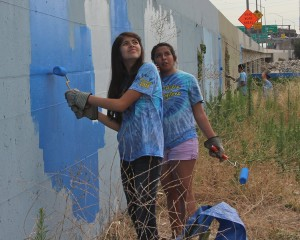 Amigos volunteers painting over grafitti